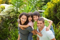 Matriz e pai que dão a crianças um sobreposto Imagens de Stock