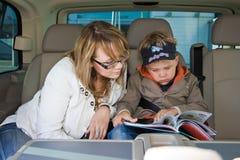 A matriz e seu filho estão lendo um livro Fotos de Stock Royalty Free