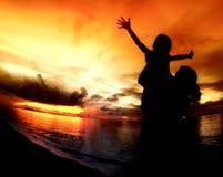 Matriz e suas silhuetas dos miúdos na praia Fotos de Stock Royalty Free
