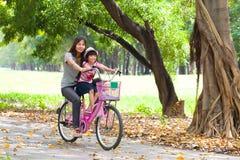 Matriz e uma bicicleta de ciclagem da filha Fotografia de Stock