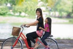 Matriz e uma bicicleta de ciclagem da filha Imagem de Stock