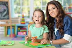 A matriz ensina o miúdo fazer artigos do ofício foto de stock