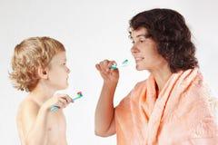 A matriz ensina seu filho pequeno escovar seus dentes imagens de stock
