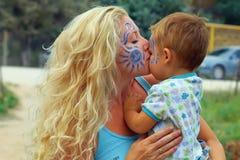 matriz Face-pintada que beija sua criança pequena Foto de Stock