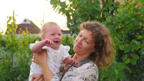 Matriz feliz com bebé O bebê com cara de sorriso está acenando nas mãos da mãe video estoque