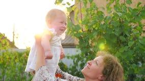 Matriz feliz com bebé O bebê com cara de sorriso está acenando nas mãos da mãe Reflexão da lente video estoque
