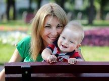 Matriz feliz com o filho no parque Imagem de Stock