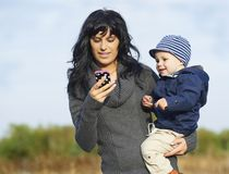 Matriz feliz com o rapaz pequeno no telemóvel Fotos de Stock Royalty Free