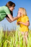 Matriz feliz e filha que riem no campo Fotos de Stock