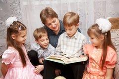 Matriz feliz e quatro crianças que lêem um livro. Imagem de Stock Royalty Free