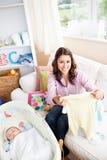 A matriz feliz que desembala o bebê veste-se em casa fotos de stock