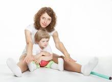 A matriz feliz que faz o esporte exercita com filha pequena Fotos de Stock Royalty Free