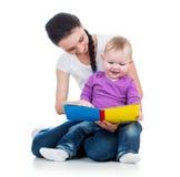Matriz feliz que lê um livro para caçoar a menina Imagem de Stock