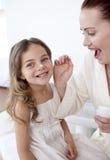 Matriz feliz que põr o creme sobre a face da sua filha fotografia de stock royalty free
