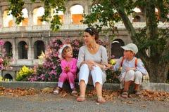 Matriz, filho e filha sentando-se perto de Colosseum imagens de stock royalty free