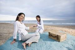 Matriz latino-americano e criança que têm o piquenique na praia Fotos de Stock
