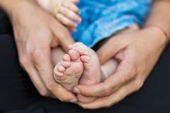 A matriz mantem delicadamente o pé do bebê disponivel imagem de stock royalty free
