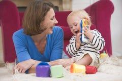 Matriz na sala de visitas que joga com bebê Fotografia de Stock Royalty Free