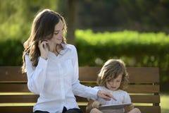 Matriz no telefone com a filha que usa a tabuleta digital Imagens de Stock