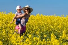 A matriz nova e sua filha relaxam no campo Imagens de Stock Royalty Free