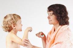 A matriz nova ensina seu filho escovar seus dentes imagem de stock