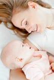 Matriz nova feliz e seu bebê que encontram-se na cama imagens de stock royalty free