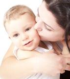 Matriz nova feliz que beija um bebê Fotografia de Stock