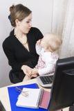 Matriz ocupada com seu bebê Fotografia de Stock