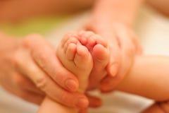 A matriz prende delicadamente o pé do bebê imagem de stock royalty free