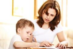 Matriz que ajuda nos trabalhos de casa a seu filho fotos de stock royalty free