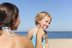 Matriz que aplica a loção do suntan a sua filha fotografia de stock royalty free