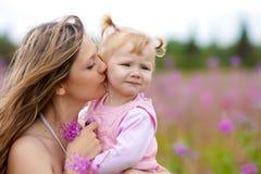 Matriz que beija a filha no prado ao ar livre Fotografia de Stock