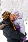 Matriz que beija sua filha no inverno imagem de stock royalty free