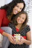 Matriz que dá a filha seu presente de Natal Fotos de Stock Royalty Free