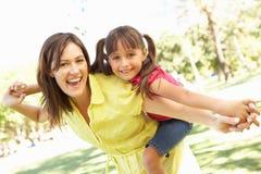 A matriz que dá o passeio da filha suporta sobre no parque fotos de stock