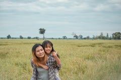 A matriz que dá o passeio da filha suporta sobre no parque Retrato de feliz fotos de stock royalty free