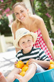 Matriz que empurra o filho no Wheelbarrow Foto de Stock Royalty Free
