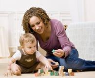 Matriz que joga com blocos do alfabeto com seu filho Fotografia de Stock