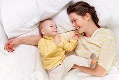 Matriz que joga com o bebê na cama Imagens de Stock
