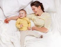 Matriz que joga com o bebê na cama Imagem de Stock Royalty Free