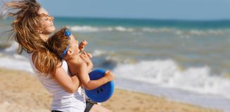 Matriz que joga com o filho no fundo da praia fotos de stock royalty free