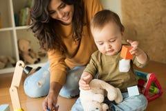 Matriz que joga com seu bebê Foto de Stock
