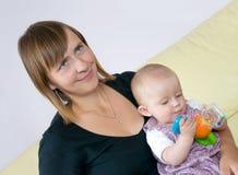 Matriz que sorri e jogo do bebê fotografia de stock