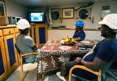 Matrosemannschaft an Bord eines Schiffs oder eines Schiffes, die Spaß fernsehend hat lizenzfreie stockfotos