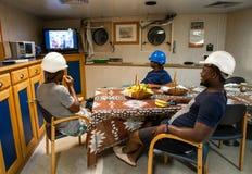 Matrosemannschaft an Bord eines Schiffs oder eines Schiffes, die Spaß fernsehend hat lizenzfreie stockfotografie