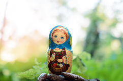 Matryoshka in the brite forest. Beautiful handmade doll in the forest royalty free stock photography