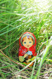 Matryoshka in the brite green grass. Beautiful handmade doll in the grass stock images