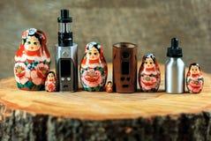 Matryoshka familj och e-cigarett Vaping saker och ryssdocka på en trätabell Ryssland vape arkivbild