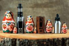 Matryoshka family and e-cigarette. Vaping things and russian doll on a wooden table. Russia vape. Royalty Free Stock Photos