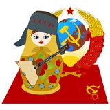 Matryoshka in fur cap with a balalaika. Russian nesting doll in the fur cap with a musical instrument on the background of the coat of arms of the USSR. The Stock Image
